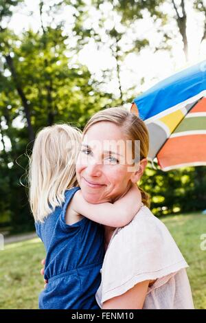 Portrait of mid adult woman and toddler daughter hugging in park - Stock Photo