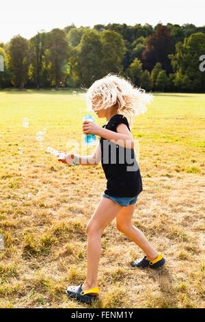 Girl waving bubble wand and making bubbles in park - Stock Photo