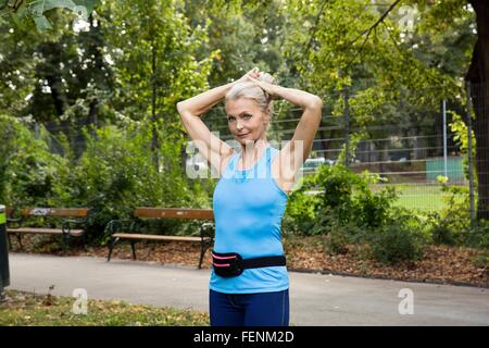Mature woman tying up hair whilst training in park - Stock Photo