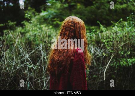 Rear View Of Woman Standing In Forest - Stock Photo