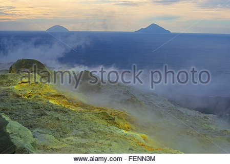Sulphur and fumarole smoke at Gran Cratere and view of islands, Vulcano Island, Aeolian Islands, Sicily, Italy - Stock Photo