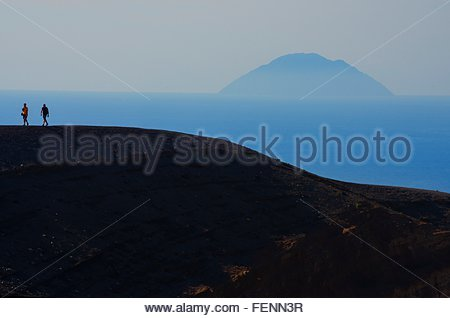 Two silhouetted tourists walking crater rim, Vulcano Island, Aeolian Islands, Sicily, Italy - Stock Photo