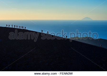 Large group of silhouetted tourists walking rim at Gran Cratere, Vulcano Island, Aeolian Islands, Sicily, Italy - Stock Photo