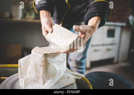 Cropped view of mid adult mans hands removing clay block from plastic bag - Stock Photo