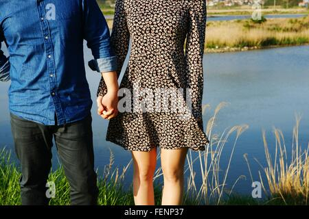 Mid Section Of Couple Holding Hands - Stock Photo