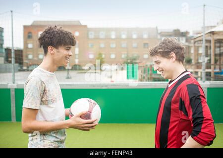 Two young men playing football on urban football pitch - Stock Photo