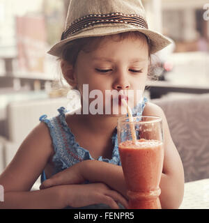 Fun kid girl in hat drinking smoothie juice from glass in street city cafe. Toned closeup portrait - Stock Photo