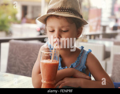 Fun kid girl in hat drinking smoothie juice from glass in street city cafe - Stock Photo