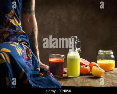 Cropped view of  woman wearing dress sitting on table with raw juices in glass bottle and jars - Stock Photo