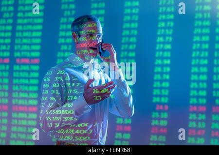 Businessman using mobile phone with projected financial data - Stock Photo