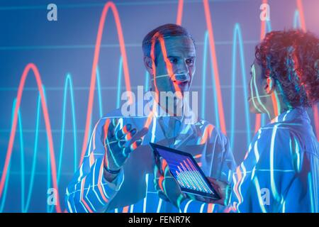 Scientists in discussion with graphical data projection - Stock Photo