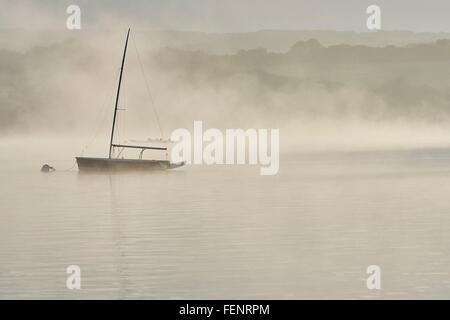 Silhouetted yacht on misty Wimbleball lake at dawn, Exmoor, Somerset, England - Stock Photo