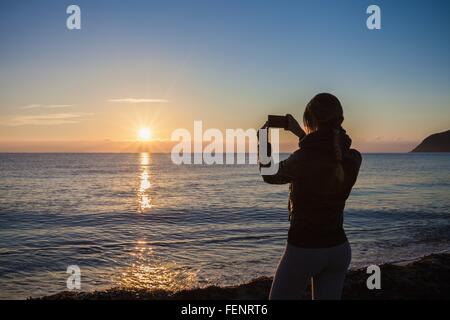 Rear silhouetted view of young woman photographing sunset over sea, Villasimius, Sardinia, Italy - Stock Photo