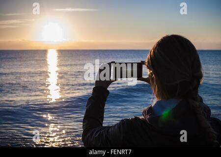 Over shoulder silhouetted view of young woman photographing sunset over sea, Villasimius, Sardinia, Italy - Stock Photo