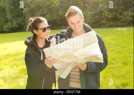 Young couple reading map in field - Stock Photo