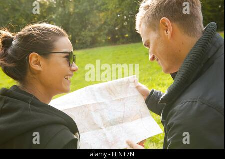 Over the shoulder view of young couple reading map in field - Stock Photo