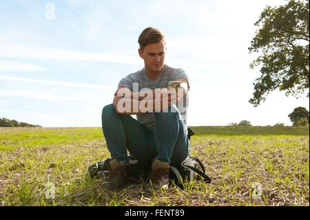 Young man sitting on backpack reading smartphone texts in field - Stock Photo