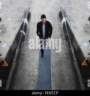 High Angle View Of Handsome Young Man Walking Down Street - Stock Photo