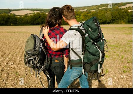 Rear view of romantic young hiking couple in field, Great Missenden, Buckinghamshire, U.K - Stock Photo