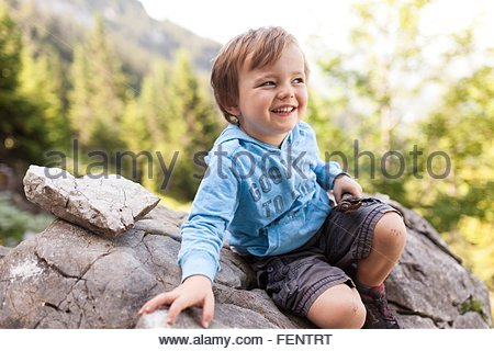 Portrait of young boy sitting on rock - Stock Photo