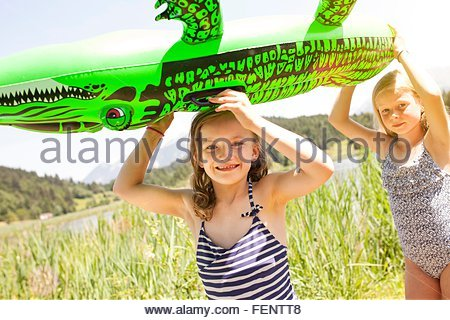 Two young girls walking through field, carrying inflatable crocodile - Stock Photo