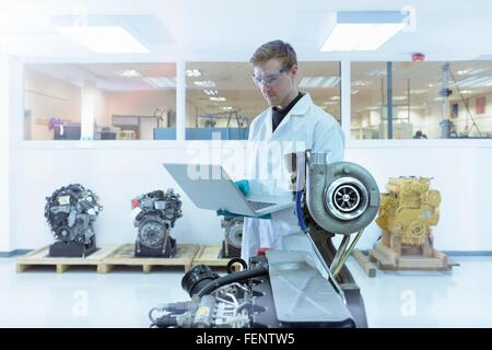 Scientist using laptop in turbo charger automotive research laboratory - Stock Photo