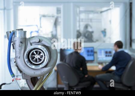 Scientists working at computers in turbo charger automotive research laboratory - Stock Photo