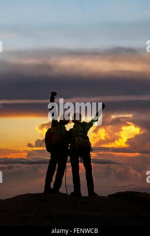 Climbers exulting on mountain top at sunset, Mont Blanc, France - Stock Photo