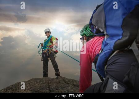 Climber on mountain top holding rope for partner, Mont Blanc, France - Stock Photo