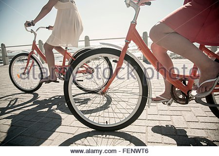 Young women cycling on seafront, Cape Town, South Africa - Stock Photo