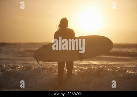 Silhouette of young male surfer carrying surfboard in sea, Devon, England, UK - Stock Photo