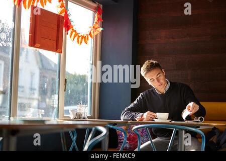 Young man alone in cafe drinking coffee and reading magazine