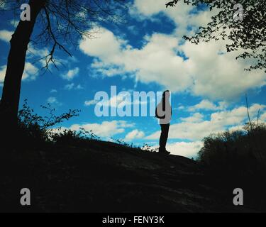 Silhouette Of Woman Standing On Rock - Stock Photo