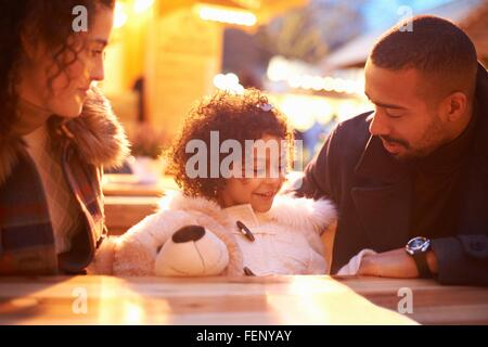 Girl at amusement park holding teddy bear sitting at table with parents - Stock Photo