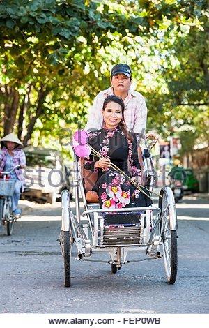 Vietnamese woman in Ao Dai dress on rickshaw, Hue, Thua Thien-Hue Province, Vietnam - Stock Photo