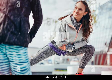 Two female runners doing warm up stretches in city - Stock Photo