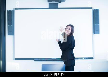 Young woman in office using whiteboard, looking over shoulder at camera smiling - Stock Photo