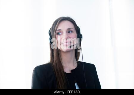 Young woman wearing telephone headset looking away smiling - Stock Photo