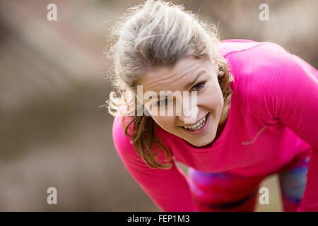 Young woman wearing sportswear bending over exhausted - Stock Photo