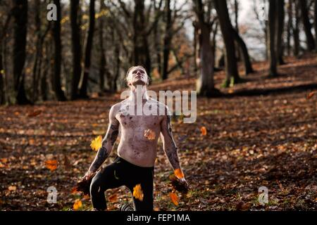 Bare chested tattooed man kneeling on autumn leaf covered forest floor looking up - Stock Photo