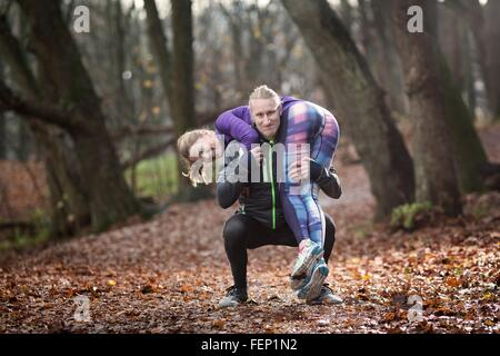 Mid adult man crouching in forest carrying young woman on shoulders looking at camera smiling - Stock Photo