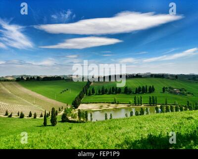 High Angle View Of Green Field Against Cloudy Sky - Stock Photo