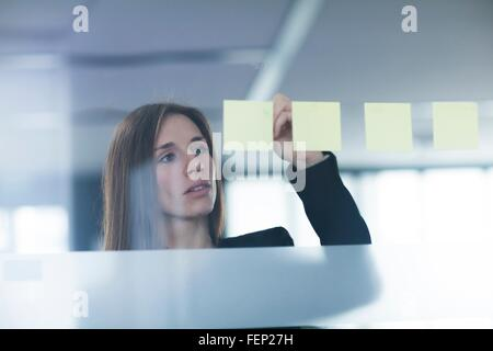 View through window of young woman writing on post it note stuck to glass - Stock Photo