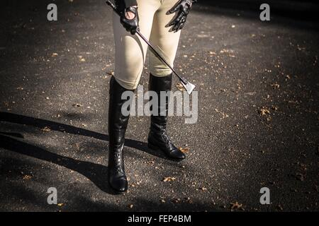Woman wearing riding boots, holding riding crop, low section - Stock Photo