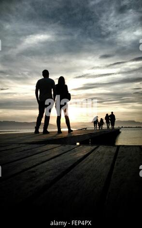 Rear View Of People Standing On Pier In Front Of River Against Cloudy Sky - Stock Photo