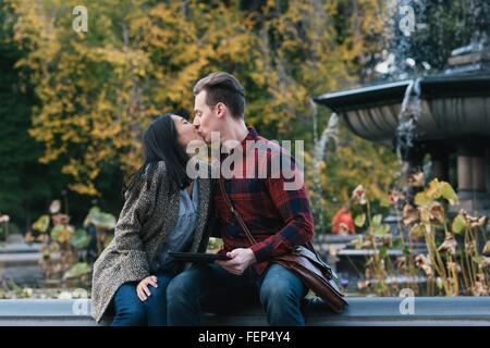 Mid adult couple kissing at Bethesda fountain in Central Park, New York, USA - Stock Photo