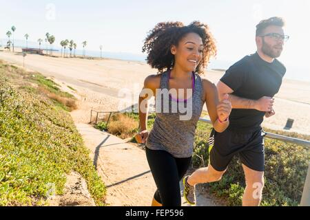 Couple running along pathway by beach - Stock Photo