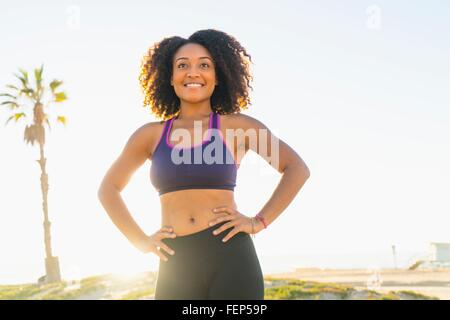 Portrait of mid adult woman, hands on hips, smiling, outdoors - Stock Photo