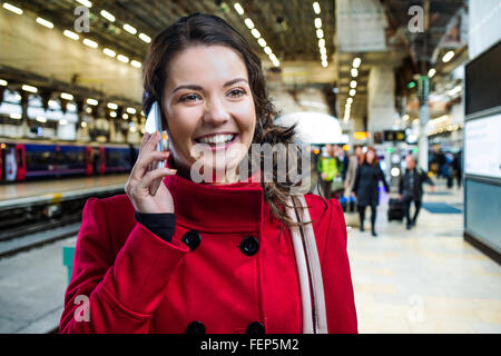 Woman in red coat on train station talking on phone - Stock Photo