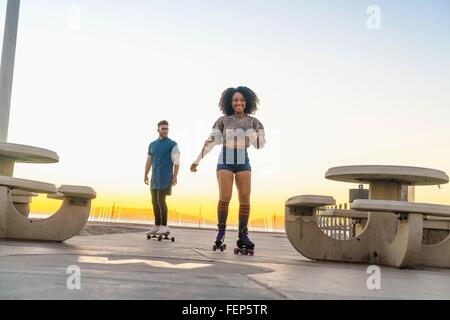 Young man on skateboard, following mid adult woman on rollerskates - Stock Photo